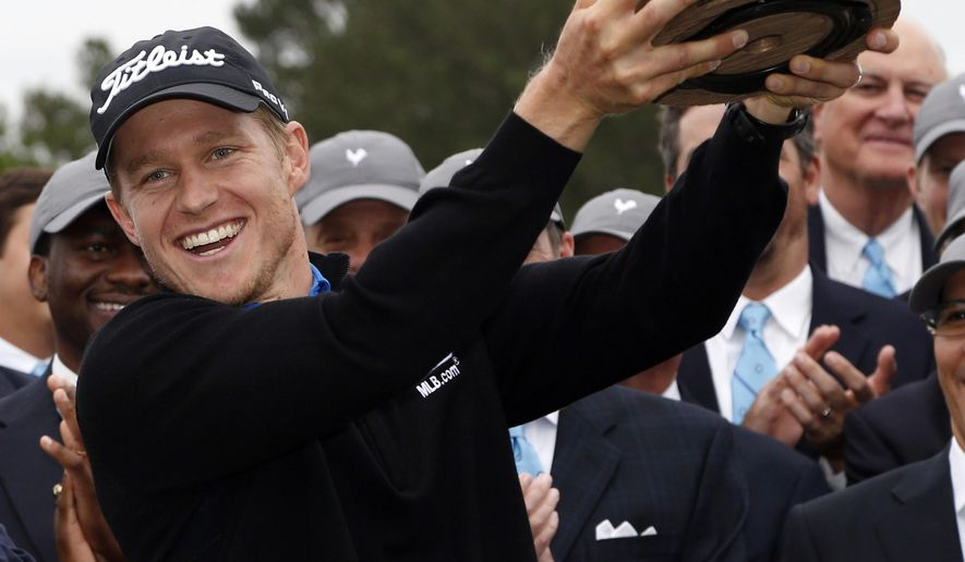 "Peter Malnati shows off ""Reveille,"" the trophy of the Sanderson Farms Championship after winning for the first time on the PGA Tour, closing with a 5-under 67 to win in Jackson, Miss., Monday, Nov. 9, 2015. Malnati finished at 18 under in for the tournament. (AP Photo/Rogelio V. Solis)"