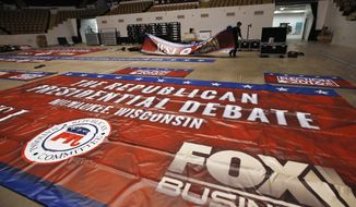 Workers put up banners in preparation for Tuesday's Republican debate, Monday, Nov. 9, 2015, in Milwaukee. (AP Photo/Morry Gash)