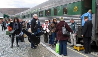 In this Saturday Nov. 7, 2015 photo, travelers board the Roots on the Rails music train in Bellows Falls, Vt. The special train made its first East Coast Trip between Bellows Falls and Rutland, Vt., where about 50 passengers spent the day listening to music while riding in vintage rail cars of the Green Mountain Railroad rolling through the countryside. (AP Photo/Wilson Ring)