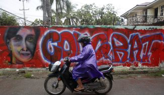 A man rides past graffiti congratulating Myanmar's opposition leader Aung San Suu Kyi in her party's election victory in Mandalay, Myanmar, Wednesday Nov. 11, 2015. Suu Kyi has won her parliamentary seat, official results showed Wednesday, leading a near total sweep by her party that will give the country its first government in decades that isn't under the military's sway. (AP Photo/Hkun Lat)
