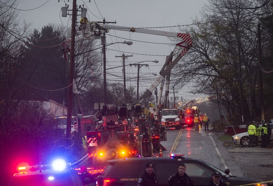 Emergency personnel and electrical crews work at the scene where authorities say a small business jet crashed into an apartment building in Akron, Ohio, Tuesday, Nov. 10, 2015. Investigators were trying to determine how many people were on the 10-seater jet, but they confirmed two deaths, said Lt. Sierjie Lash, an Akron fire department spokeswoman. AP Photo/Phil Long)
