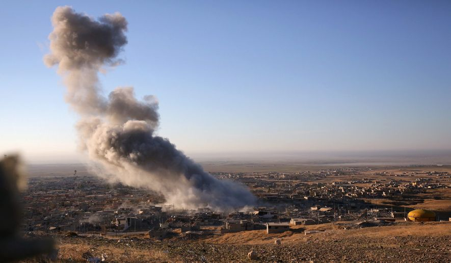Smoke believed to be from an airstrike billows over the northern Iraqi town of Sinjar on Thursday, Nov. 12. Kurdish Iraqi fighters, backed by the U.S.-led air campaign, launched an assault Thursday aiming to retake the strategic town of Sinjar, which the Islamic State overran last year in an onslaught that caused the flight of tens of thousands of Yazidis and first prompted the U.S. to launch airstrikes against the militants. (Associated Press)