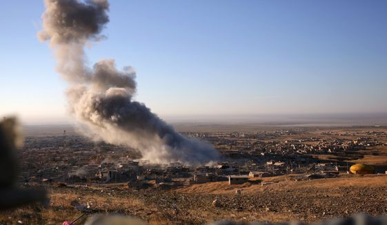 Smoke believed to be from an airstrike billows over the northern Iraqi town of Sinjar on Thursday, Nov. 12, 2015. Kurdish Iraqi fighters, backed by the U.S.-led air campaign, launched an assault Thursday aiming to retake the strategic town of Sinjar, which the Islamic State overran last year in an onslaught that caused the flight of tens of thousands of Yazidis and first prompted the U.S. to launch airstrikes against the militants. (AP Photo/Bram Janssen)