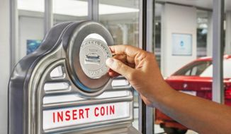 Car buyers can insert a Carvana-branded coin into the vending machine slot and deliver your car from the Tower to you in seconds. (Photo by Business Wire)