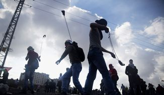 Palestinian protesters use slingshots to throw stones towards Israeli security forces during clashes following a protest marking the 11th anniversary of the death of late Palestinian leader Yasser Arafat, in the West Bank city of Ramallah, Wednesday, Nov. 11, 2015. (AP Photo/Majdi Mohammed)
