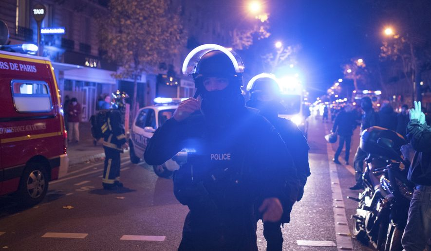 Elite police officers arrive outside the Bataclan theater in Paris, France, Wednesday, Nov. 13, 2015. Several dozen people were killed in a series of unprecedented attacks around Paris on Friday, French President Francois Hollande said, announcing that he was closing the country's borders and declaring a state of emergency. (AP Photo/Kamil Zihnioglu)