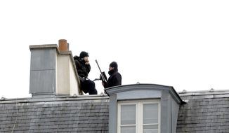 Snippers take position atop a building in front of the Elysee palace in Paris, Saturday, Nov. 14, 2015. French President Francois Hollande vowed to attack the Islamic State group without mercy as the jihadist group admitted responsibility Saturday for orchestrating the deadliest attacks inflicted on France since World War II. (AP Photo/Jacques Brinon)
