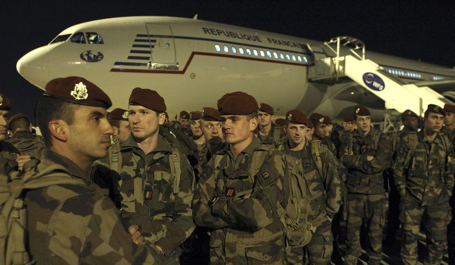 Soldiers stand on the tarmac of the Charles de Gaulle airport, north of Paris, as part of a security reinforcements, Saturday, Nov. 14, 2015. (AP Photo/Michel Spingler)