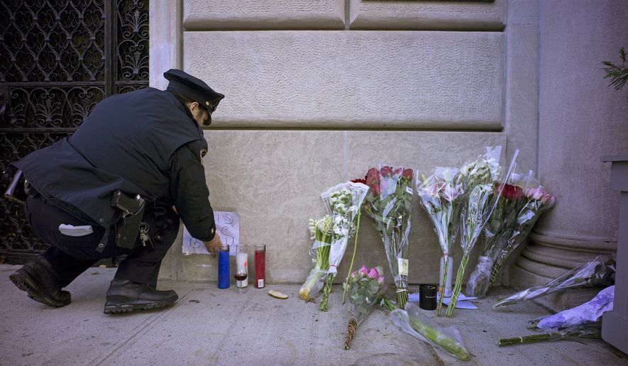 A New York City police officer adjusts parts of a make shift memorial left as a sign of support to France near the door of the French consulate in New York, Saturday, Nov. 14, 2015. French officials say several dozen people were killed in shootings and explosions at a theater, restaurant and elsewhere in Paris on Friday. (AP Photo/Craig Ruttle)