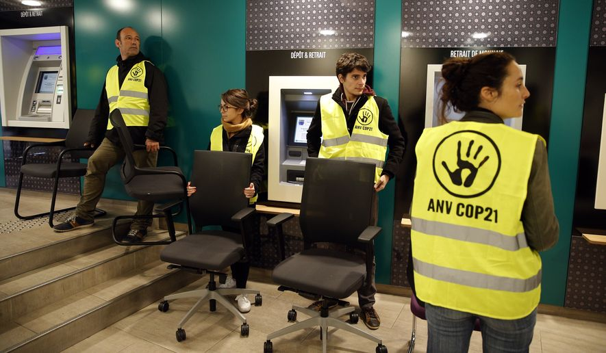 Activists in Paris take chairs from a bank to protest tax evasion, one of many actions linked to the climate conference known as COP21. A march and other activities have been canceled, however, as a result of terrorist attacks in the city last week. (Associated Press)