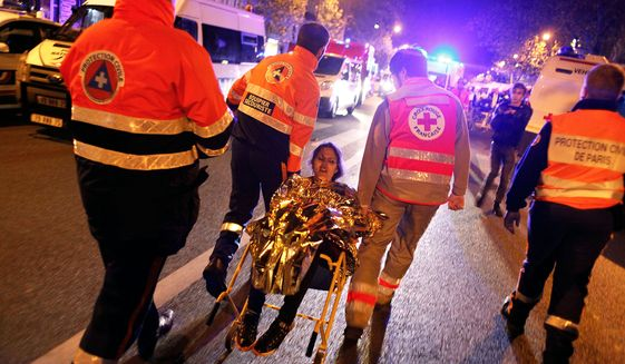 A person is being evacuated after a shooting, outside the Bataclan theater in Paris, Saturday, Nov. 14, 2015. A series of attacks targeting young concert-goers, soccer fans and Parisians enjoying a Friday night out at popular nightspots killed over 100 people in the deadliest violence to strike France since World War II.(AP Photo/Thibault Camus)