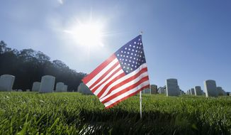 An American flag sits in front of gravestones on Veterans Day at San Francisco National Cemetery in the Presidio of San Francisco, Wednesday, Nov. 11, 2015. (AP Photo/Jeff Chiu)