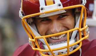 Washington Redskins quarterback Kirk Cousins (8) smiles while standing along the sidelines during the second half of an NFL football game against the New Orleans Saints in Landover, Md., Sunday, Nov. 15, 2015. The Redskins defeated the New Orleans Saints 47-14. (AP Photo/Evan Vucci)