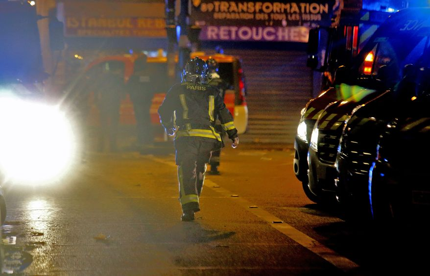 A rescue worker runs after an explosion in the 10th district of Paris, Friday, Nov. 13, 2015. Several dozen people were killed Friday in a series of terror attacks, the deadliest to hit Paris since World War II, French President Francois Hollande said, announcing that he was closing the country's borders and declaring a state of emergency. (AP Photo/Jacques Brinon)