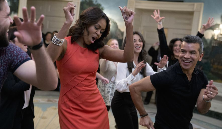 "First lady Michelle Obama dances to Gloria Estefan's ""Conga"" in the Diplomatic Room of the White House in Washington, Monday, Nov. 16, 2015, during a Broadway at the White House event for high school students involved in performing arts programs. She is joined by Sergio Trujillo, Colombian dancer and choreographer, right, and Josh Segarra, left.  (AP Photo/Carolyn Kaster)"