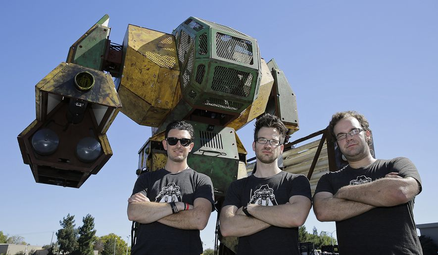 MegaBots founders from left, Brinkley Warren, Matt Oehrlein and Gui Cavalcanti stand below their 15-foot tall, piloted Mk.II robot at the Pioneer Summit in Redwood City, Calif., in this Oct. 9, 2015, file photo. (AP Photo/Eric Risberg)