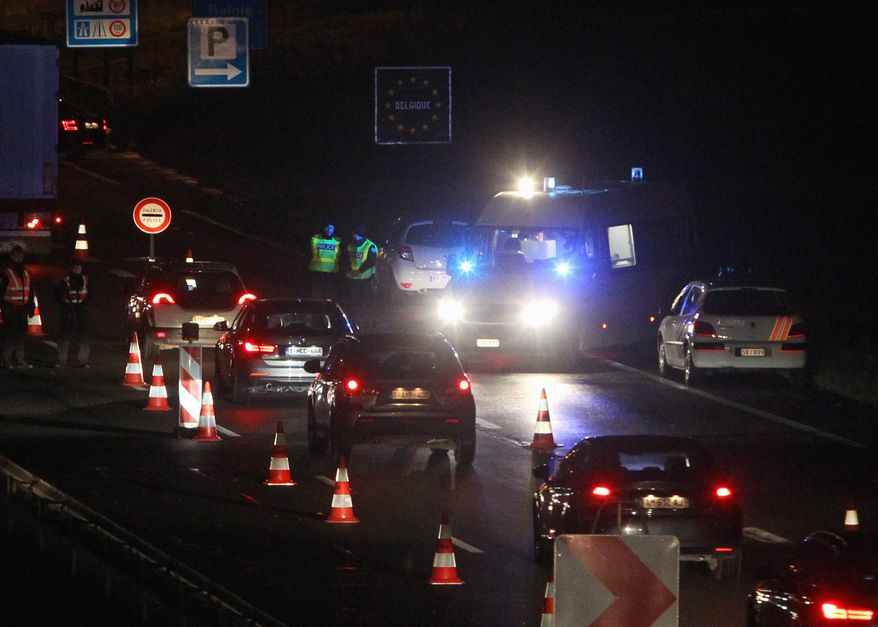 French police check vehicles at the border crossing between France and Belgium as part of the hunt for fugitives in the Paris attacks. (Associated Press)