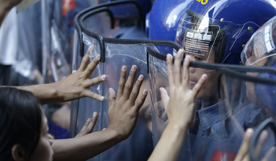 Student protesters clash with police near the U.S. Embassy ahead of the Asia-Pacific Economic Cooperation (APEC) summit in Manila, Philippines Tuesday, Nov. 17, 2015. Leaders of the 21 countries and territories that make up the Asia-Pacific Economic Cooperation forum have begun arriving for the two day meeting which begins here Nov. 18. (AP Photo/Mark Baker)