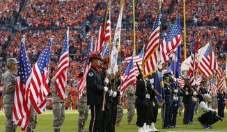 Servicemen carry American flags onto the field to celebrate Salute to Service month during an NFL football game between the Denver Broncos and the Kansas City Chiefs, Sunday, Nov. 15, 2015, in Denver. (AP Photo/Jack Dempsey)