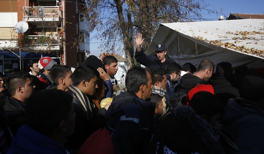 Serbian police officer attempt to organize migrants queuing to get registered at a refugee center in the southern Serbian town of Presevo, Monday, Nov. 16, 2015. Refugees fleeing war by the tens of thousands fear the Paris attacks could prompt Europe to close its doors, especially after police said a Syrian passport found next to one attacker's body suggested its owner passed through Greece into the European Union and on through Macedonia and Serbia last month. (AP Photo/Darko Vojinovic)