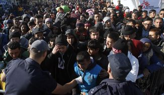 Serbian police officers trying to organise migrants queuing to get registered at a refugee center in the southern Serbian town of Presevo, Monday, Nov. 16, 2015. Refugees fleeing war by the tens of thousands fear the Paris attacks could prompt Europe to close its doors, especially after police said a Syrian passport found next to one attacker's body suggested its owner passed through Greece into the European Union and on through Macedonia and Serbia last month. (AP Photo/Darko Vojinovic)