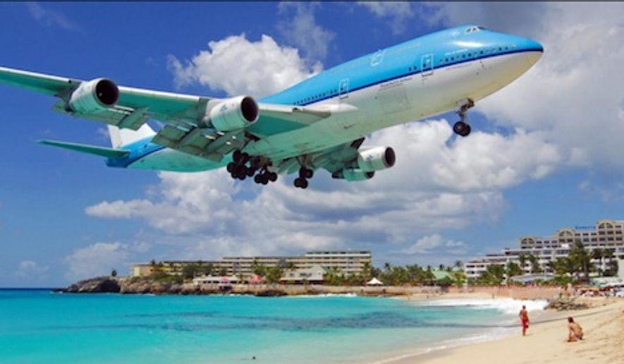 A commercial airliner buzzes a tourist beach as it lands at Princess Juliana International Airport in St. Maarten. (Image: www.sxmairport.com)