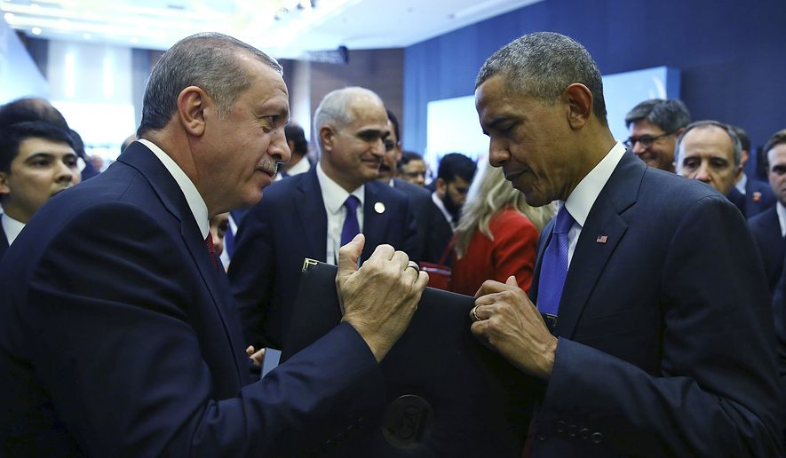 Turkish President Recep Tayyip Erdogan, left, presents a photo album to U.S. President Barack Obama at the end of the G-20 Summit in Antalya, Turkey, Monday, Nov. 16, 2015. The leaders of the Group of 20 wrapped up their two-day summit near the Turkish Mediterranean coastal city of Antalya Monday against the backdrop of heavy French bombardment of the Islamic State's stronghold in Syria. The bombings marked a significant escalation of France's role in the fight against the extremist group. (Anadolu Agency via AP, Pool)