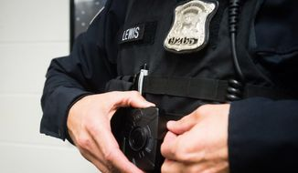 Bay City Police officer Brad Lewis puts on a Taser body-worn camera on Monday, Nov. 16, 2015, at the Bay City Police Department in Michigan. (Yfat Yossifor/The Bay City Times via AP) ** FILE **