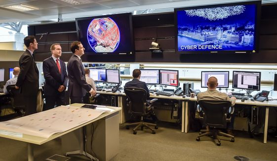 Britain's Chancellor of the Exchequer George Osborne is shown the 24 hour Operations Room by the Director of GCHQ Robert Hannigan, center, and Cheltenham MP Alex Chalk at GCHQ in Cheltenham, England, Tuesday, Nov. 17, 2015. Treasury chief George Osborne says the country will double the amount of funds devoted to fighting cyber-crime. Osborne says the Islamic State group is looking to gain the capability to attack infrastructure such as air traffic control or electrical systems. (Ben Birchall/PA via AP) UNITED KINGDOM OUT - NO SALES - NO ARCHIVES