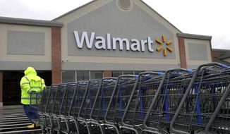A worker pulls a line of shopping carts toward a Wal-Mart store in North Kingstown, R.I., in this Nov. 13, 2012, file photo. (AP Photo/Steven Senne)