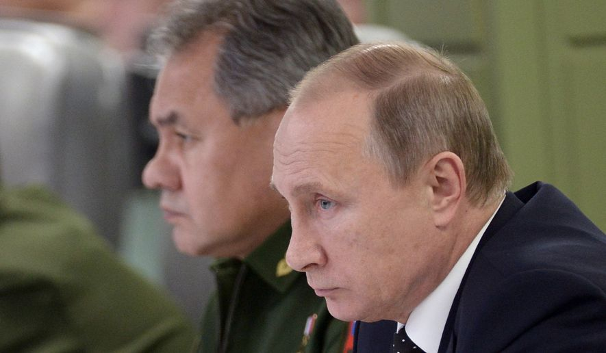 Russian President Vladimir Putin, right, flanked by Defense Minister Sergei Shoigu, visits the National Defense Control Center in Moscow, Tuesday, Nov. 17, 2015. (Alexei Nikolsky/SPUTNIK, Kremlin Pool Photo via AP)