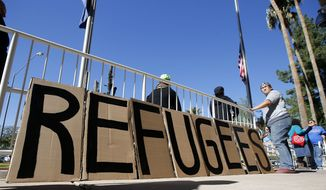 A sign welcoming Syrian refugees is placed at the entrance to the office of the Arizona governor during a rally at the Arizona Capitol Tuesday, Nov. 17, 2015, in Phoenix.   Arizona Gov. Doug Ducey has joined a growing number of governors calling for an immediate halt to the placement of any new refugees in the wake of terrorist attacks in Paris.  The U.S. State Department says Arizona has received 153 Syrian refugees so far this year. (AP Photo/Ross D. Franklin)
