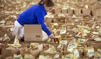 """Eight-year-old Lily Kostopoulos, daughter of Wilkes-Barre/Scranton Penguins hockey team captain Tom Kostopoulos, helps fill bags of food to be distributed to those in need for Thanksgiving at a distribution center in Wilkes-Barre Twp., Pa. on Sunday, Nov. 15, 2015. Wives, family members and girlfriends of Penguins players volunteered their time to help out the 36th annual """"Thanksgiving Project"""" sponsored by the Commission on Economic Opportunity and the Weinberg Northeast Regional Food Bank.           (Christopher Dolan / The Citizens' Voice via AP)"""