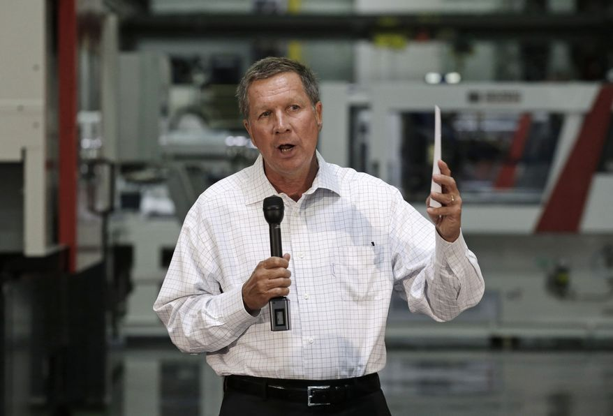 Ohio Gov. John Kasich discusses the state budget with members of local business organizations during a meeting at manufacturing equipment maker Milacron LLC in Batavia, Ohio, in this July 18, 2013, file photo. (AP Photo/Al Behrman, File)
