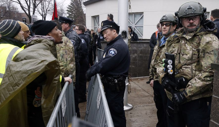 A Black Lives Matter supporter, left, talks to Minneapolis police guarding the Fourth Precinct entrance, Wednesday, Nov. 18, 2015, in Minneapolis. It was the fourth day of protests of the killing of 24-year-old Jamar Clark, an unarmed black man, by a Minneapolis police officer. (AP Photo/Jim Mone) ** FILE **
