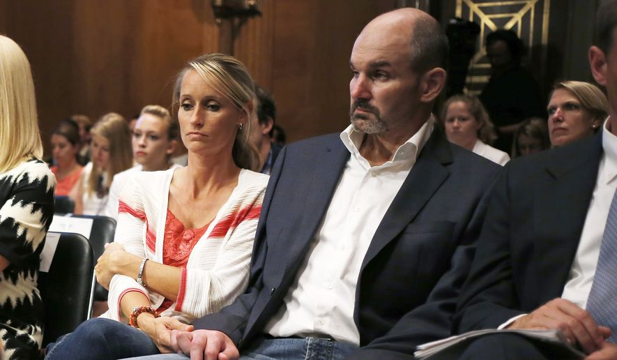 Former NFL football player Kevin Turner, right, who suffers from Lou Gehrig's disease, listens during testimony before the Senate Special Committee on Aging hearing regarding concussions and the long-term effects of brain-related sports injuries in Washington, in this June 25, 2014, file photo. (AP Photo/Charles Dharapak, File)