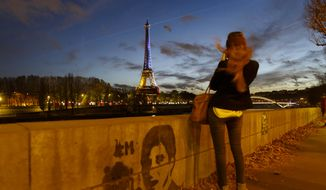 A girl takes a picture from the banks of the River Seine of the illuminated Eiffel Tower in the French national colors red, white and blue in honor of the victims of the terrorist attacks last Friday, in Paris, Wednesday, Nov. 18, 2015. (AP Photo/Daniel Ochoa de Olza)