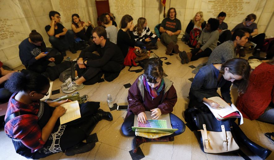 Students gather inside Nassau Hall during a sit-in, Thursday, Nov. 19, 2015, in Princeton, N.J. The protesters from a group called the Black Justice League, who staged a sit-in inside university President Christopher Eisgruber's office on Tuesday, demand the school remove the name of former school president and U.S. President Woodrow Wilson from programs and buildings over what they said was his racist legacy. (AP Photo/Julio Cortez)