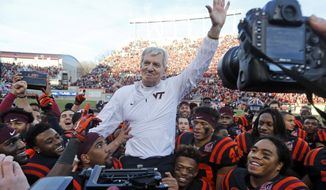 Virginia Tech head coach Frank Beamer is carried off the field by his players after an NCAA college football game in Blacksburg, Va., Saturday, Nov. 21, 2015. North Carolina won the game 30-27 in overtime, but it was Beamer's last home game as coach since he is retiring at the end of the season. (AP Photo/Steve Helber)
