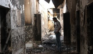 An employee of Doctors Without Borders walks inside the charred remains of their hospital after it was hit by a U.S. airstrike in Kunduz, Afghanistan. (Najim Rahim via AP)