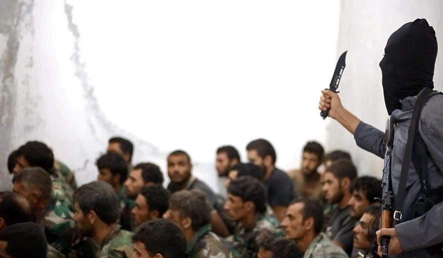 A fighter from the Islamic State group stands next to captured Syrian army soldiers following the battle for the Tabqa air base in Raqqa, Syria, on Aug. 27, 2014. (Raqqa Media Center of the Islamic State group)