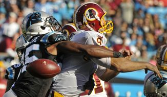 Washington Redskins' Kirk Cousins, right, fumbles the ball as he is hit by Carolina Panthers' Bene' Benwikere, left, in the second half of an NFL football game in Charlotte, N.C., Sunday, Nov. 22, 2015. The Panthers recovered the ball. (AP Photo/Mike McCarn)