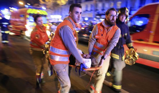 A woman is evacuated from the Bataclan concert hall after a shooting in Paris, in this Nov. 13, 2015, file photo. (AP Photo/Thibault Camus, File)