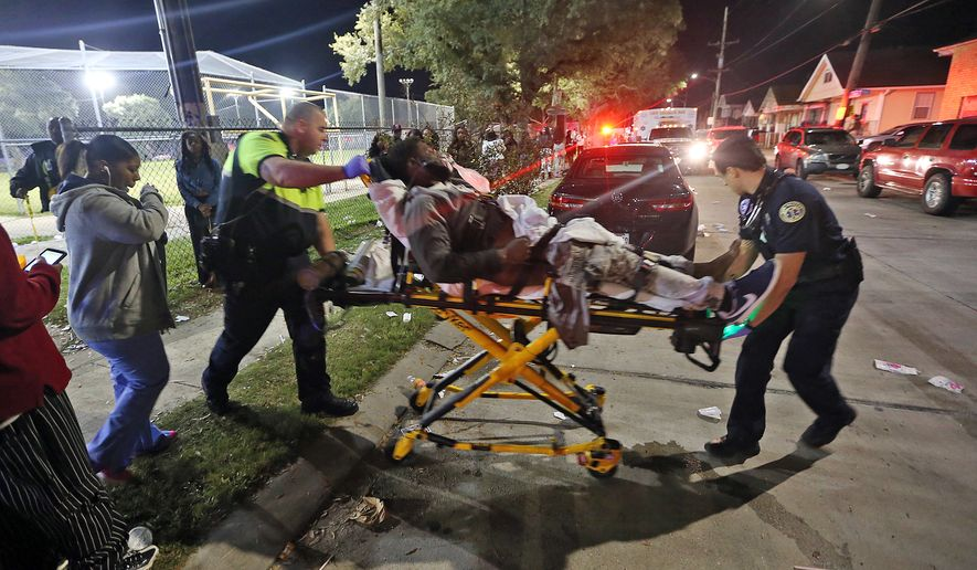 Officials remove a man from the scene following a shooting in New Orleans' 9th Ward on Sunday, Nov. 22, 2015. (The Times-Picayune via Associated Press)