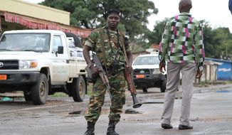 A Burundian  soldier with his gun and rocket launcher guard a deserted street in Bujumbura, Burundi, Sunday, Nov. 8, 2015.  Witnesses say seven people have been killed in an overnight attack at a bar in the violence-prone Burundi capital, Bujumbura. Witnesses on Sunday said they heard gunshots Saturday night at a bar in the Kanyosha neighborhood of Bujumbura, and later found bloodied bodies lying on the floor. (AP Photo)