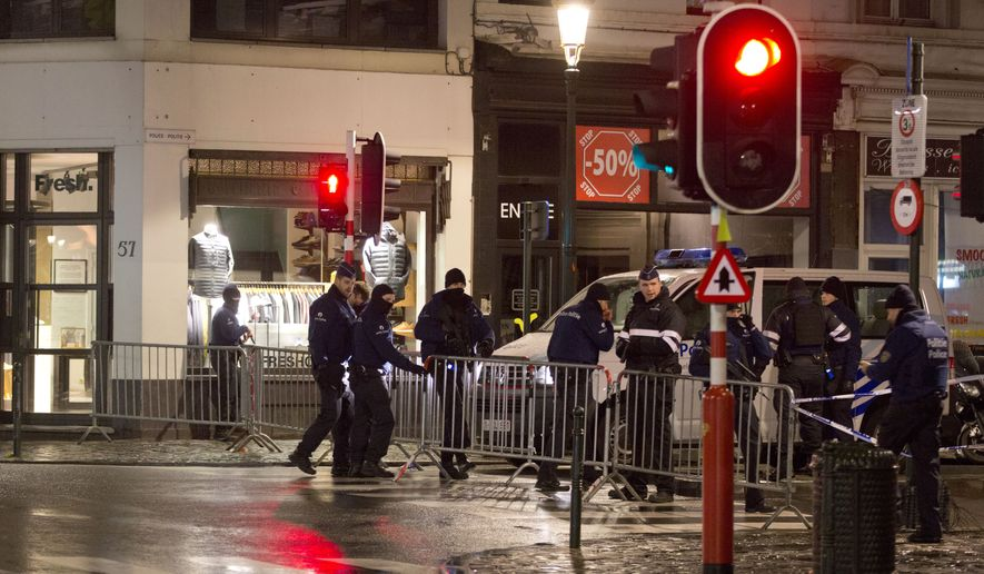 Police set up a barricade during an operation in the center of Brussels on Sunday, Nov. 22, 2015. (AP Photo/Virginia Mayo)