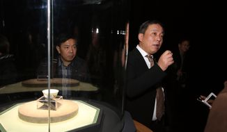 Chinese billionaire and art collector Liu Yiqian, right, speaks at an opening ceremony in Shanghai, China, for the exhibition of a $36 million Ming Dynasty tea cup, at left, he bought and paid for with his American Express card, in this Dec. 18, 2014, file photo. (Chinatopix via AP)