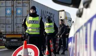 French police officers monitor the border between France and Belgium in Neuville-en-Ferrain, northern France, Monday, Nov. 23, 2015. Belgian police launched more raids in Brussels and beyond early Monday, detaining five more people as they continued their hunt for a fugitive suspect in the Paris attacks. (AP Photo/Michel Spingler)