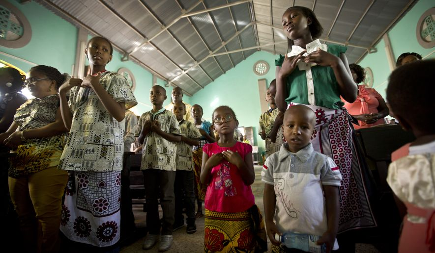 In this photo taken Sunday, Nov. 8, 2015, young members of the congregation sing and pray during a service at the St. Peter's Catholic Church in Garissa, Kenya. This Kenyan town in which Islamic extremists killed nearly 150 at a college of mostly Christian students in April offers a snapshot of what France and Lebanon, both targeted in recent attacks, and other countries face - the challenge of harmonizing Christian-Muslim relations at a time of danger from extremists - an issue that Pope Francis is expected to address during his trip Nov. 25-30 to Kenya, Uganda and the Central African Republic. (AP Photo/Ben Curtis)