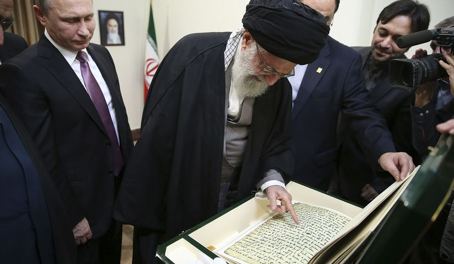 In this Monday, Nov. 23, 2015, photo released by the official website of the office of the Iranian supreme leader, Supreme Leader Ayatollah Ali Khamenei, center, looks at a copy of Koran, Islam's holy book, presented by Russian President Vladimir Putin, left, during their meeting in Tehran, Iran. (Office of the Iranian Supreme Leader via AP)